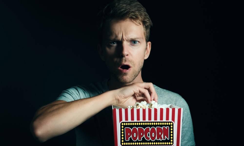 man with popcorn watching netflix